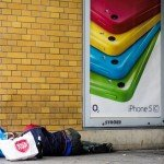 Homeless person next to iPhone advertsing / Flickr / Sascha Kohlmann / CC BY-SA 2.0